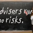 Stock Photo: Teacher showing Advisers run no risks on blackboard