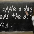 Teacher showing An apple a day keeps the doctor away on blackboa — Stock Photo