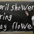 Teacher showing April showers bring May flowers on blackboard — Stock Photo