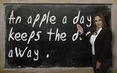 учитель, показаны яблоко в день держит доктора прочь на blackboa — Стоковое фото