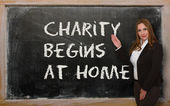 Teacher showing Charity begins at home on blackboard — Stock Photo