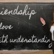 Teacher showing Friendship is love with understanding on blackbo — Stock Photo #25832767