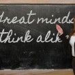 Stock Photo: Teacher showing Great minds think alike on blackboard