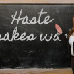 Teacher showing Haste makes waste on blackboard — Stock Photo