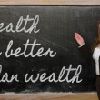 Teacher showing Health is better than wealth on blackboard — Stockfoto #25835315