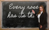 Teacher showing Every rose has its thorn on blackboard — Стоковое фото