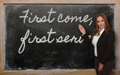 Teacher showing First come, first served on blackboard — Foto Stock