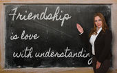 Teacher showing Friendship is love with understanding on blackbo — Stock Photo