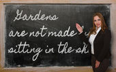 Teacher showing Gardens are not made by sitting in the shade on — Stock Photo