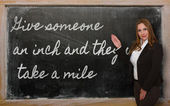 Teacher showing Give someone an inch and they will take a on bla — Stok fotoğraf
