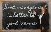 Teacher showing Good management is better than good income on bl — Стоковое фото