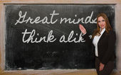 Teacher showing Great minds think alike on blackboard — Stockfoto
