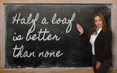 Teacher showing Half a loaf is better than none on blackboard — Photo