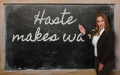 Teacher showing Haste makes waste on blackboard — Stock Photo
