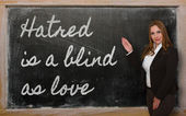 Teacher showing Hatred is a blind as love on blackboard — Stock fotografie