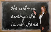Teacher showing He who is everywhere is nowhere on blackboard — Photo