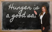 Teacher showing Hunger is a good sauce on blackboard — Stock Photo
