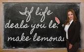 Teacher showing If life deals you lemons, make lemonade on black — Stock Photo