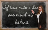 Teacher showing If two ride a horse, one must ride behind on bla — Foto de Stock
