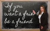 Teacher showing If you want a friend, be a friend on blackboard — Стоковое фото
