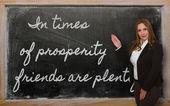 Teacher showing In times of prosperity friends are plentiful on — Stock Photo