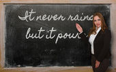 Teacher showing It never rains but it pours on blackboard — Stok fotoğraf