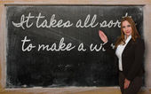 Teacher showing It takes all sorts to make a world on blackboard — ストック写真