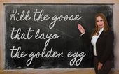 Teacher showing Kill the goose that lays the golden egg on black — Stock Photo