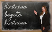 Teacher showing Kindness begets kindness on blackboard — Стоковое фото