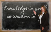 Teacher showing Knowledge in youth is wisdom in age on blackboar — ストック写真