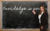 Teacher showing Knowledge is power on blackboard — 图库照片