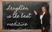 Teacher showing Laughter is the best medicine on blackboard — Photo