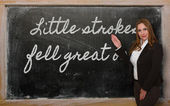 Teacher showing Little strokes fell great oaks on blackboard — Photo