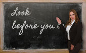 Teacher showing Look before you leap on blackboard — Стоковое фото
