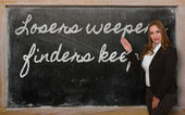 Teacher showing Losers weepers, finders keepers on blackboard — Stock Photo