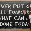 Teacher showing Never put off till tomorrow what cbe done tod — Stock Photo #25841841