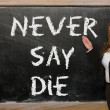 Teacher showing Never say die on blackboard — Stock Photo #25841995