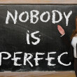 Foto de Stock  : Teacher showing Nobody is perfect on blackboard