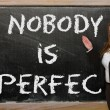 Teacher showing Nobody is perfect on blackboard — Stock Photo #25842681