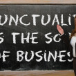 Teacher showing Punctuality is the soul of business on blackboar — Stock Photo