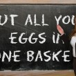 Teacher showing Put all your eggs in one basket on blackboard — Stock Photo