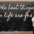 Teacher showing The best things in life are free on blackboard — Stock Photo #25847387