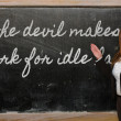 Stock Photo: Teacher showing devil makes work for idle hands on blackboar