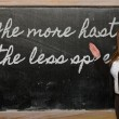 Teacher showing The more haste, the less speed on blackboard — Stock Photo