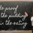 Teacher showing proof of pudding is in eating on bla — Stockfoto #25848601