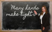Teacher showing Many hands make light work on blackboard — Stockfoto