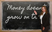 Teacher showing Money doesn t grow on trees on blackboard — Stok fotoğraf