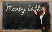 Teacher showing Money talks on blackboard — Stok fotoğraf