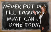 Teacher showing Never put off till tomorrow what can be done tod — Stock Photo