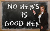 Teacher showing No news is good news on blackboard — Stock Photo